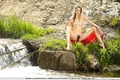 Blonde teen with a hairy pussy poses outdoors by a river