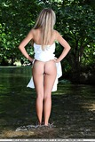 Skinny blonde babe outdoors in forest near lake