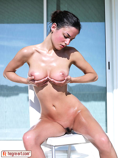 Young busty rubs her oiled body while sunbathing