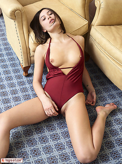 Young brunette in monokini shows tits and pussy