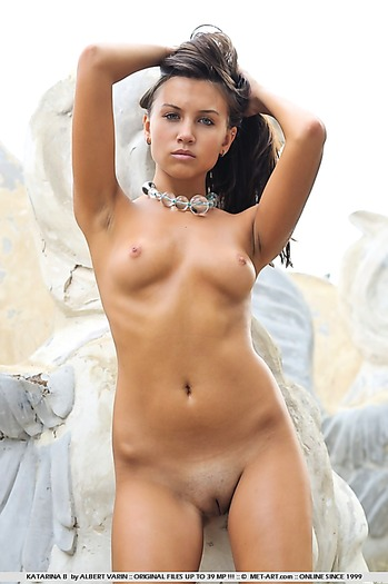 Shaved young babe with hot body poses outdoors on rocks