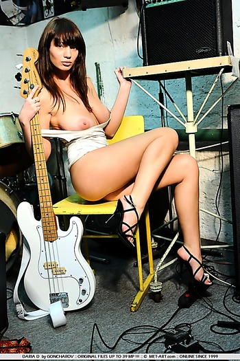 Busty babe in heels gets naked with her guitar